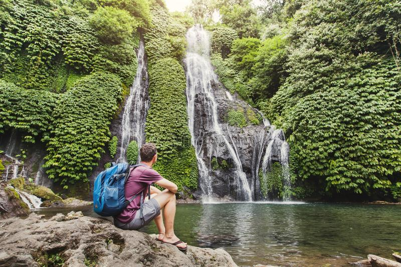 Backpacker looking at waterfall in Bali, tourism stock images