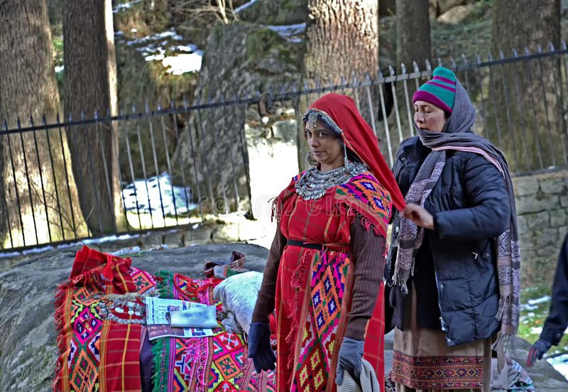 Tourist being Dressed in Traditional Attire of Kullu Valley. Manali, India – December 27, 2013: Local woman of Manali dressing a tourist in the royalty free stock photography