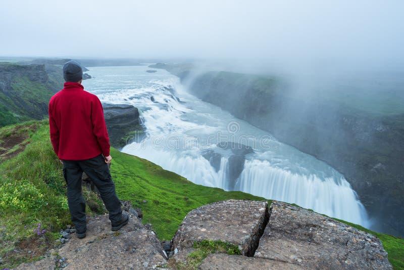 Tourist betrachtet den Gullfoss-Wasserfall in Island stockbild