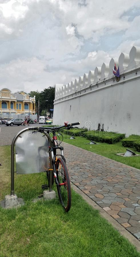 Tourist bicycle stop by Grand Palace wall in Bangkok Thailand. Tourist bike through Bangkok city visiting Grand Palace or Wat Phra Kaew. Bangkok is the most royalty free stock photo