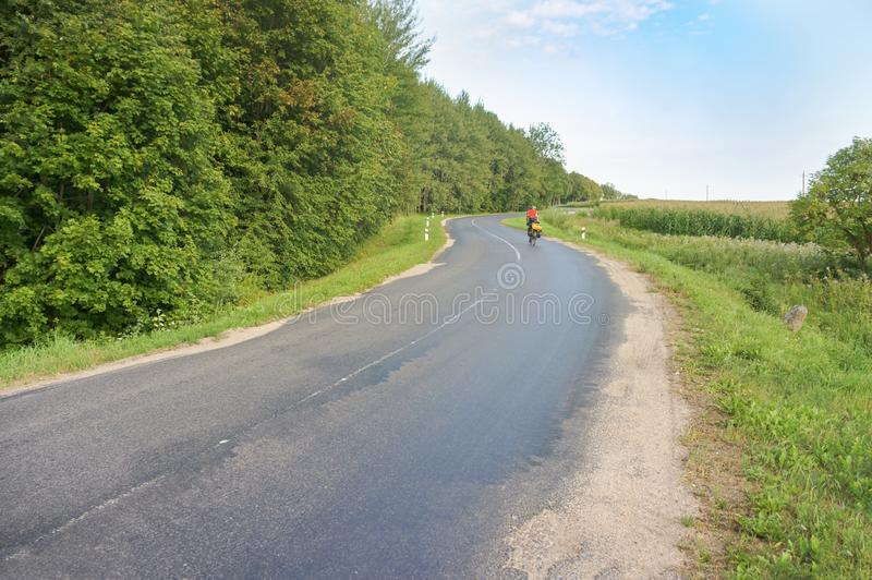 A tourist on a bike on the road, a lone cyclist royalty free stock image