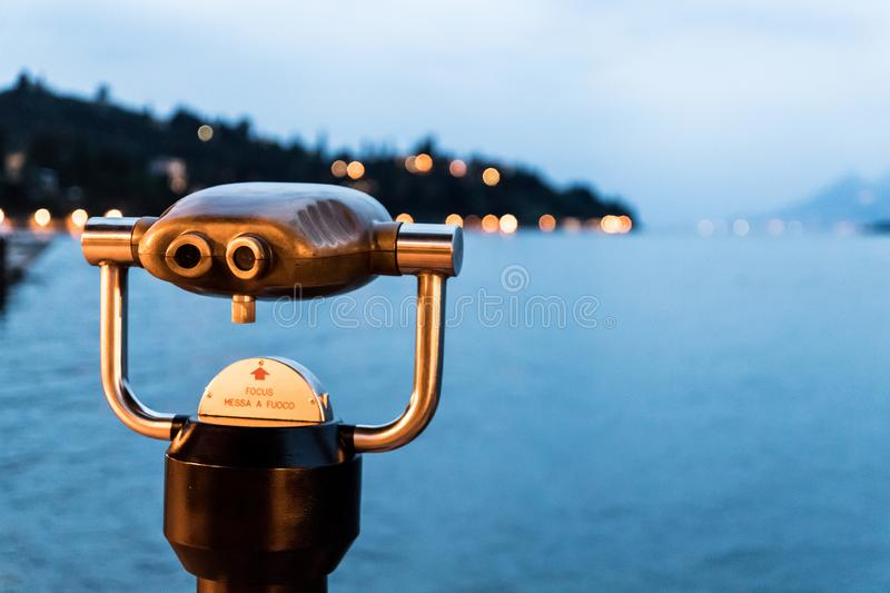 Tourist binoculars on the coastline of Lago di Garda, Italy. Tourist binoculars on the lake Lago di Garda, evening scene with water and mountains, tourism, coast royalty free stock image