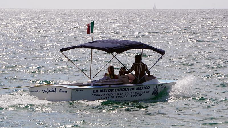 Tourist in a boat in Acapulco. Some people in a small boat travel over the sea in Acapulco mexico, touristic boat with a small flag of mexico and a blue tend stock photo