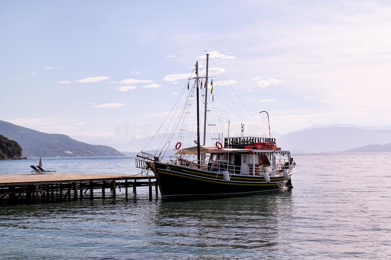 Tourist boat cruiser in small marina on sea and beautiful beach, waiting tourists for ship is sailing out of port for tourist tour. Tourist boat cruiser in small stock photo