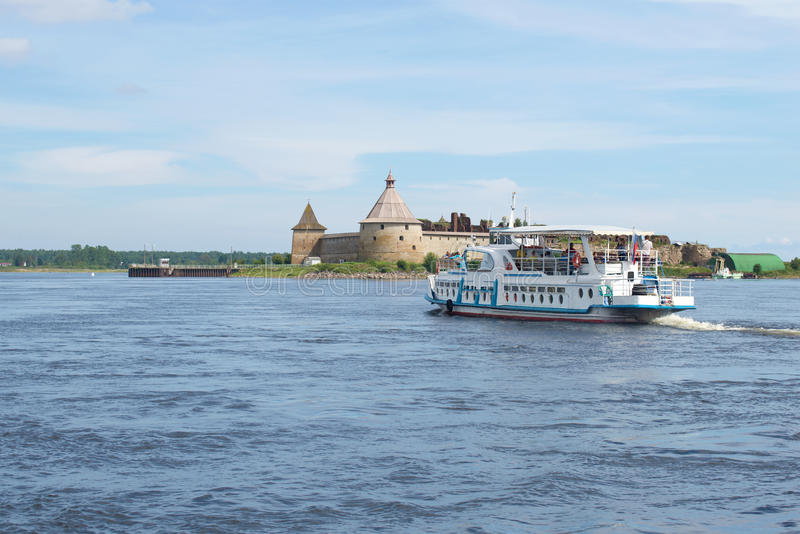 Tourist boat floats on the Neva river to the ancient russian fortress Oreshek, Russia. SHLISSELBURG, RUSSIA - AUGUST 01, 2016: Tourist boat floats on the Neva royalty free stock images