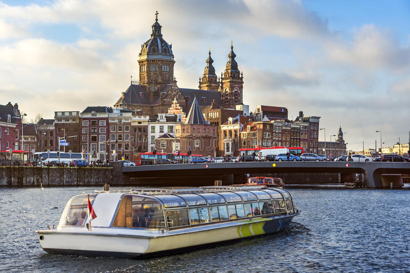 Tourist boat sailing in front the Basilica Saint Nicolas at night Amsterdam. Basilica Saint Nicolas at night Amsterdam royalty free stock photos