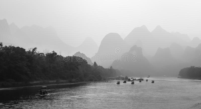 Tourist boats with tourists traveling the magnificent scenic route along the Li river. From Guilin to Yangshuo in the haze, Xingping, China. Black and white stock images