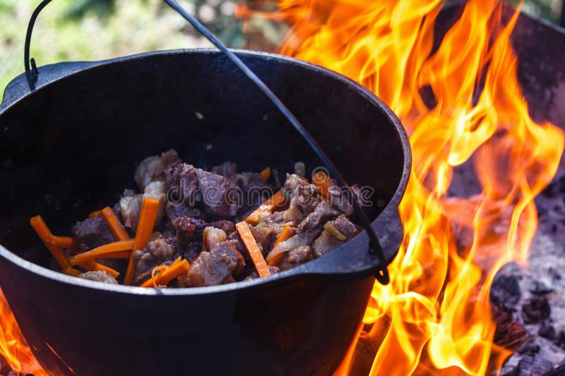 Tourist bowler with food on bonfire, cooking in the hike, outdoor activities. Preparation of pilaf. royalty free stock image