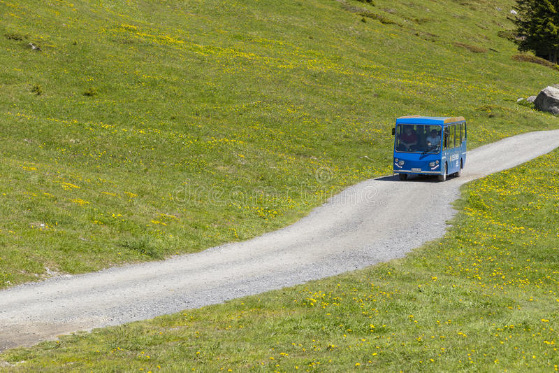 Tourist bus driving along trekking path near Oeschinensee (Oeschinen lake), on Bernese Oberland, Switzerland stock image
