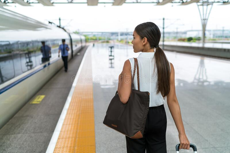 Tourist business woman leaving for trip on train with bag and luggage. Lady going on travel entering public transport royalty free stock photos