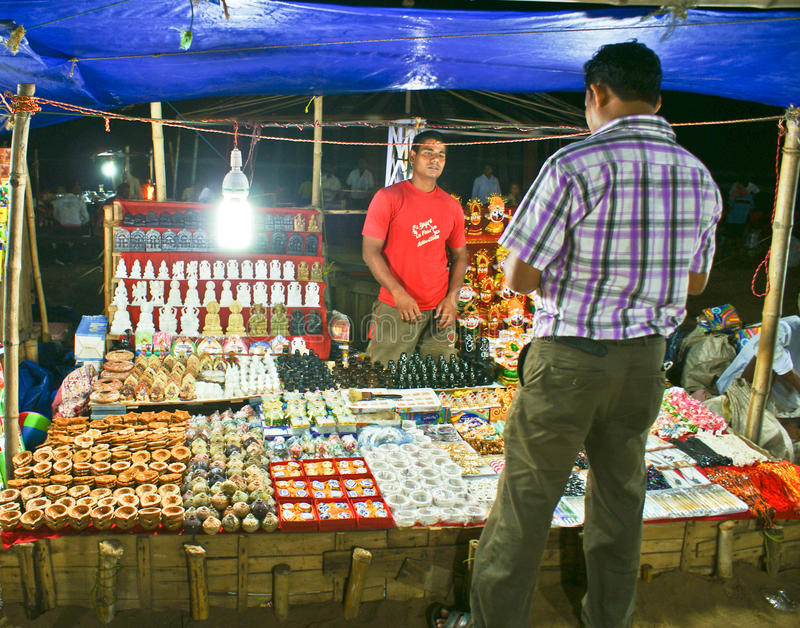 Tourist buying items from a hawker in Puri beach royalty free stock photography