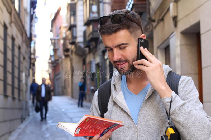 Tourist calling by phone while looking at tourism guide or dictionary stock images