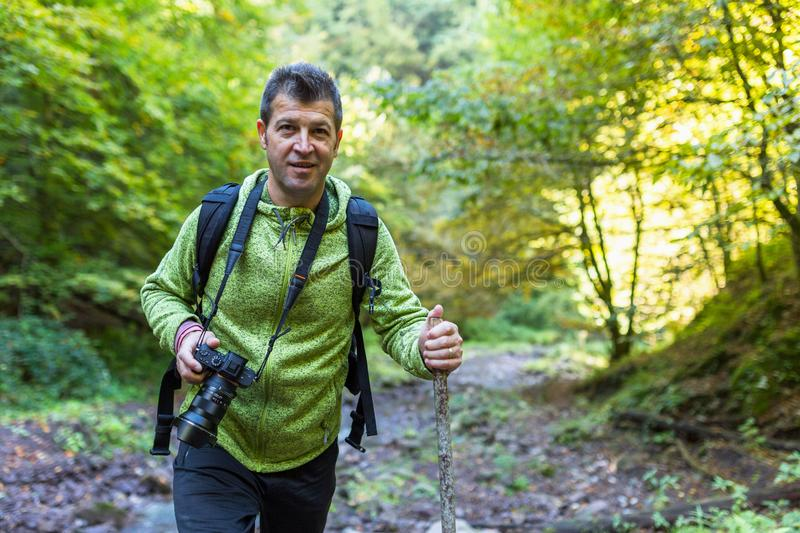Tourist with camera hiking. On a trail by the river royalty free stock images