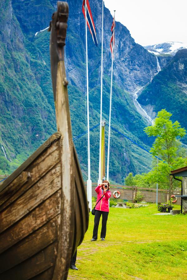Tourist with camera near old viking boat, Norway stock photo