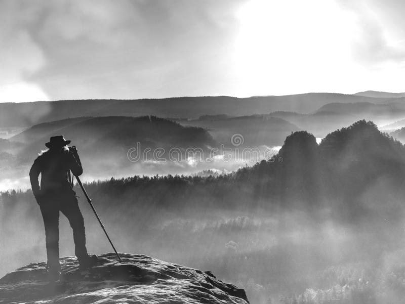 Tourist with camera shoots sunrise while standing on top of the mountain stock image