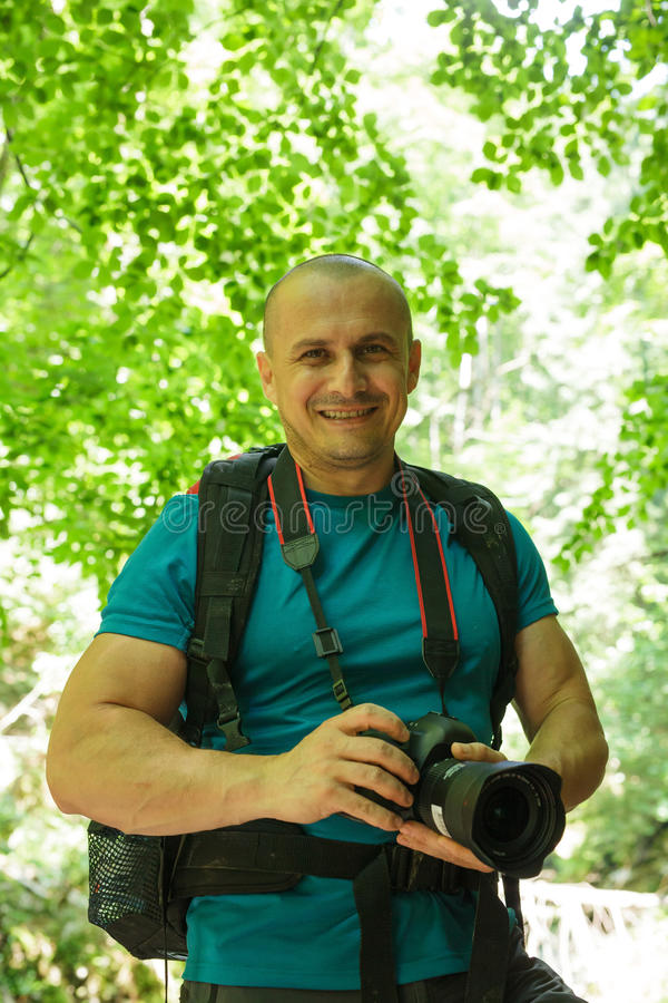 Tourist with camera on a trail. Happy tourist with camera and backpack on a trail in the forest stock images