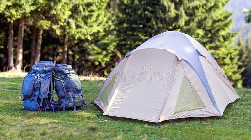 Tourist camp on green meadow with fresh grass in Carpathian mountains forest. Hikers tent and backpacks at camping site. Active l royalty free stock image