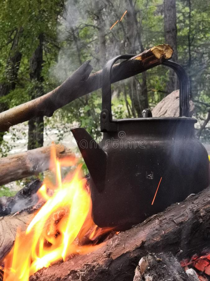 Tourist camping kettle on the fire boils on the background of the forest and the river. The romance camp royalty free stock photography