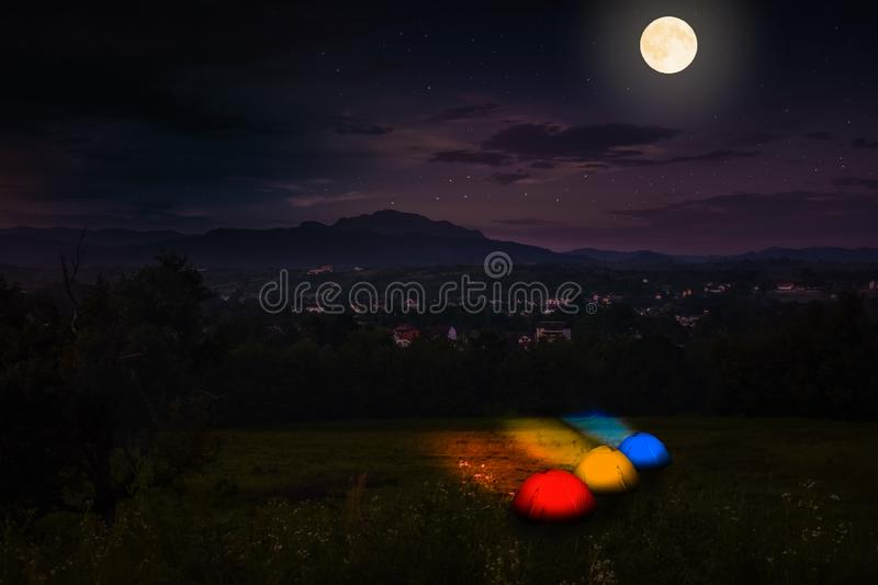 Tourist camping near forest in the night. Illuminated tent under beautiful night sky full of stars and full moon. Hiking in royalty free stock photo