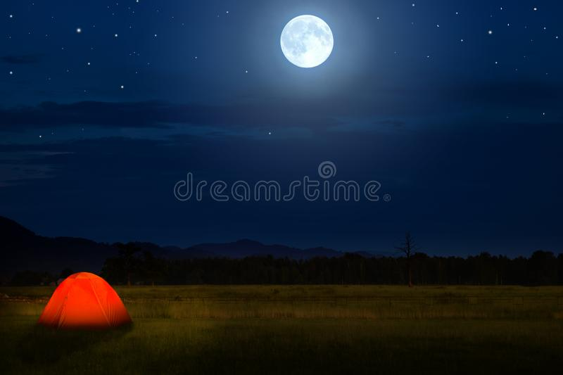 Tourist camping near forest in the night. Illuminated tent under beautiful night sky full of stars and full moon. Hiking in stock image