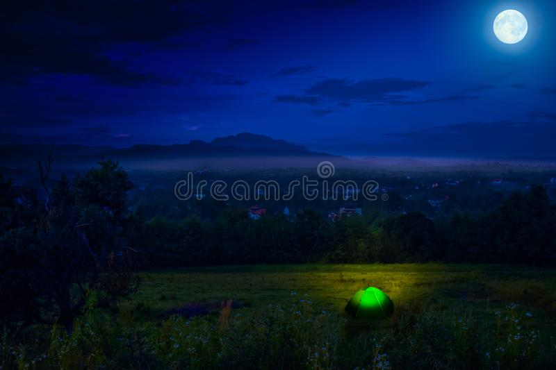 Tourist camping near forest in the night. Illuminated tent under beautiful night sky full of stars and full moon. Hiking in stock photo