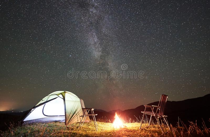 Tourist camping at night in the mountains under starry sky. Tourist camping at night in the mountains. Illuminated tent, two chairs and campfire under amazing stock image