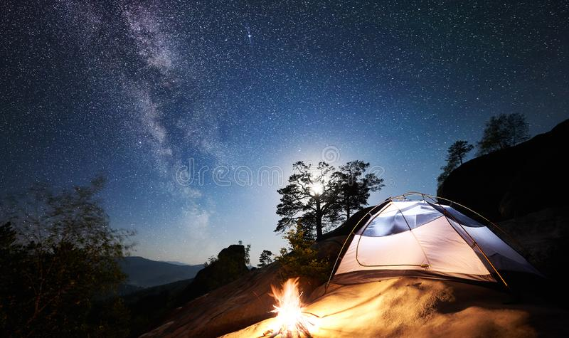 Tourist camping on rocky mountain under night starry sky royalty free stock photo