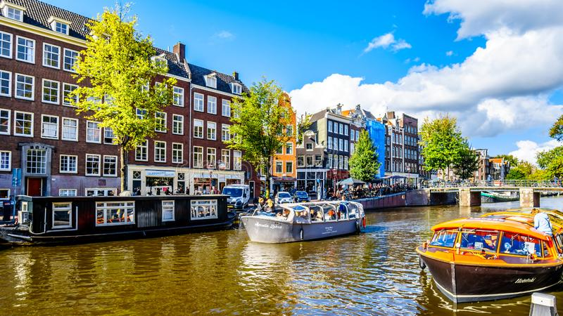 Tourist Canal Boats mooring at Anne Frank House at the Prinsengracht Prince Canal in the Jordaan neighborhood in Amsterdam royalty free stock images