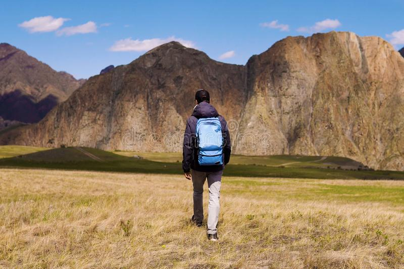 Tourist in a cap and jacket with a backpack goes on the grass in the direction of mountains. Exploring, researches and. Expedition concept royalty free stock photography