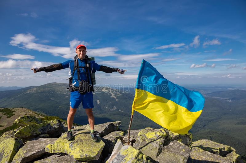 Tourist in the Carpathian mountains on the background of the flag. Traveling in the mountains stock photo