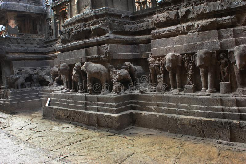 Tourist at Cave 16 with huge beasts carved around the shrine`s high plinth or platform including elephants, leonine and other best. Tourist at Cave 16 with huge royalty free stock images