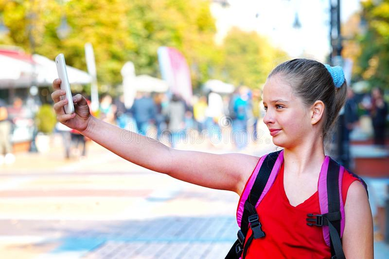 Tourist child girl with backpack taking selfies on smartphone stock photos