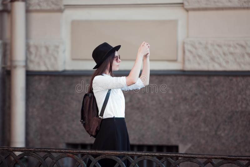 Tourist in the city takes a photo on smartphone. A young woman in a black hat and a white shirt, stock photography