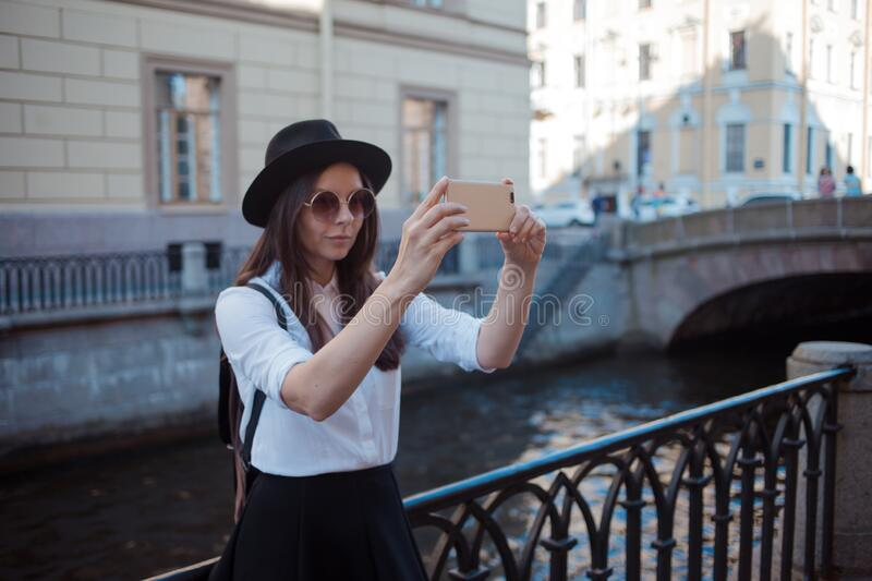 Tourist in the city takes a photo on smartphone. A young woman in a black hat and a white shirt, stock photo