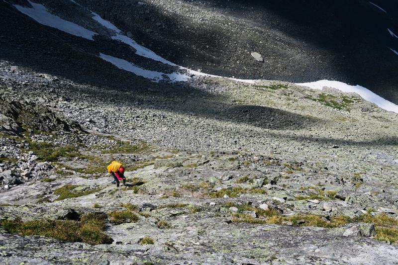 Tourist climbs up the stones in the mountains. Going up the rocky moraine royalty free stock photography