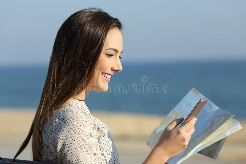 Tourist consulting location with a map and smart phone. Side view portrait of a tourist consulting location in a map and smart phone sitting on a bench on the royalty free stock images