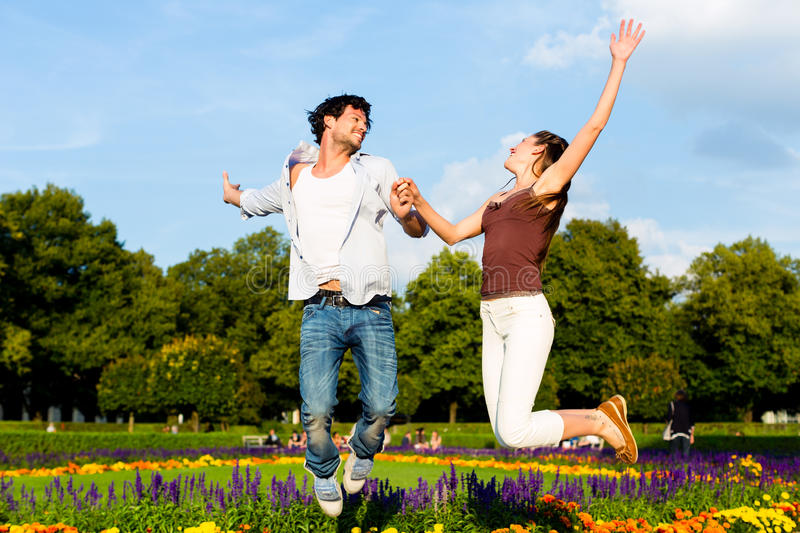 Tourist couple in city park jumping in sun royalty free stock images