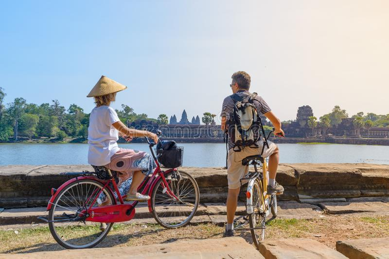Tourist couple cycling in Angkor temple, Cambodia. Angkor Wat main facade reflected on water pond. Eco friendly tourism traveling royalty free stock images