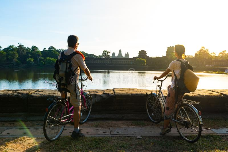 Tourist couple cycling in Angkor temple, Cambodia. Angkor Wat main facade reflected on water pond. Eco friendly tourism traveling stock photos