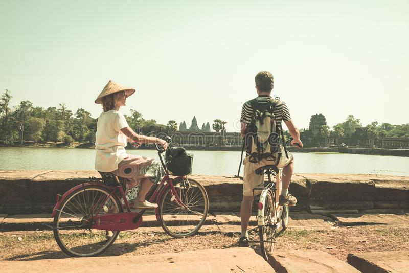 Tourist couple cycling in Angkor temple, Cambodia. Angkor Wat main facade reflected on water pond. Eco friendly tourism traveling stock photo