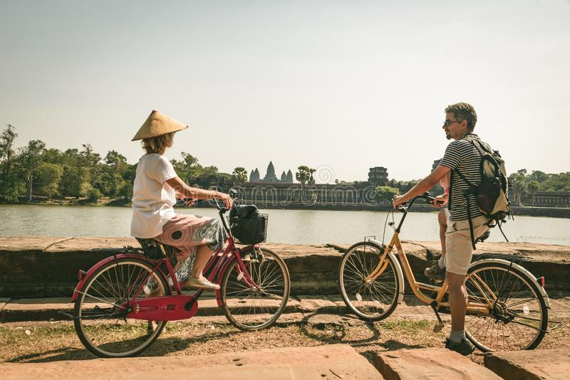 Tourist couple cycling in Angkor temple, Cambodia. Angkor Wat main facade reflected on water pond. Eco friendly tourism traveling stock images