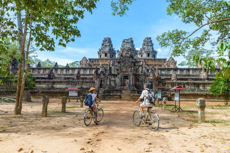 Tourist couple cycling around Angkor temple, Cambodia. Ta Keo building ruins in the jungle. Eco friendly tourism traveling stock photos