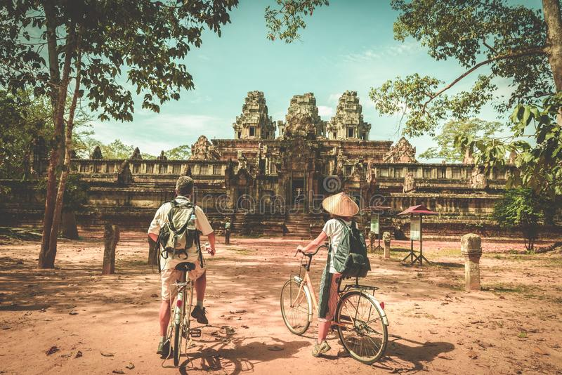 Tourist couple cycling around Angkor temple, Cambodia. Ta Keo building ruins in the jungle. Eco friendly tourism traveling, toned stock photo