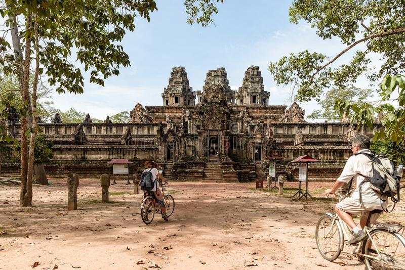 Tourist couple cycling around Angkor temple, Cambodia. Ta Keo building ruins in the jungle. Eco friendly tourism traveling, toned stock images