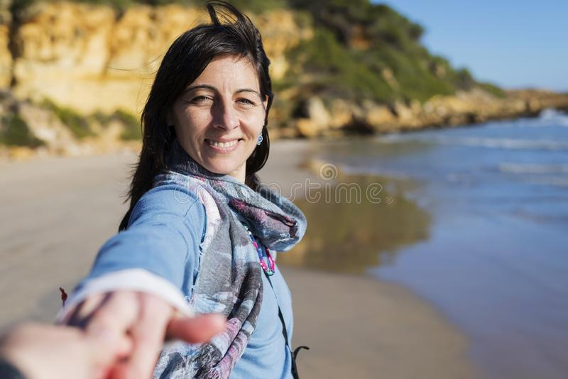 Tourist couple having fun with woman taking man by the hand and pulling towards the sea, enjoying a summer holiday together on a stock photography