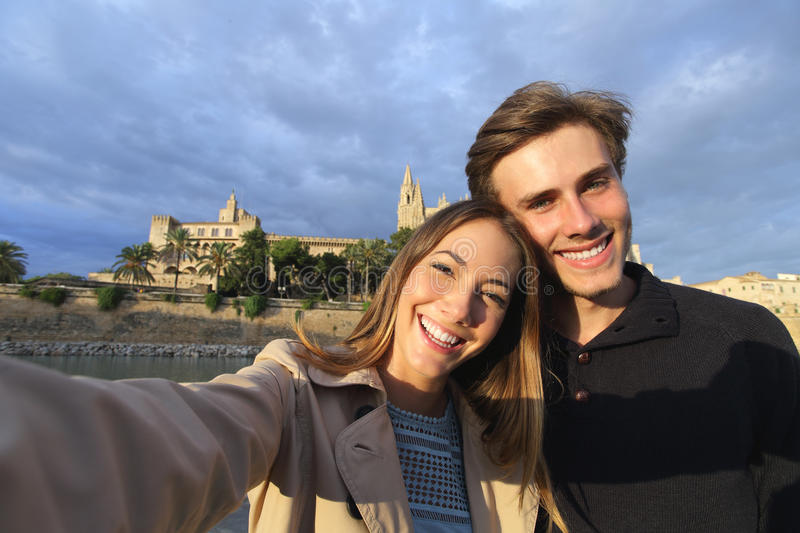 Tourist couple on holidays photographing a selfie. With Palma de Mallorca Cathedral in the background stock photo