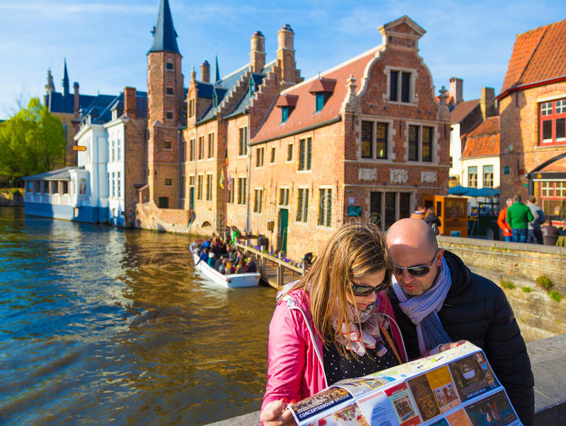 Tourist Couple Looking At Bruges Map Near Canal Editorial Photo