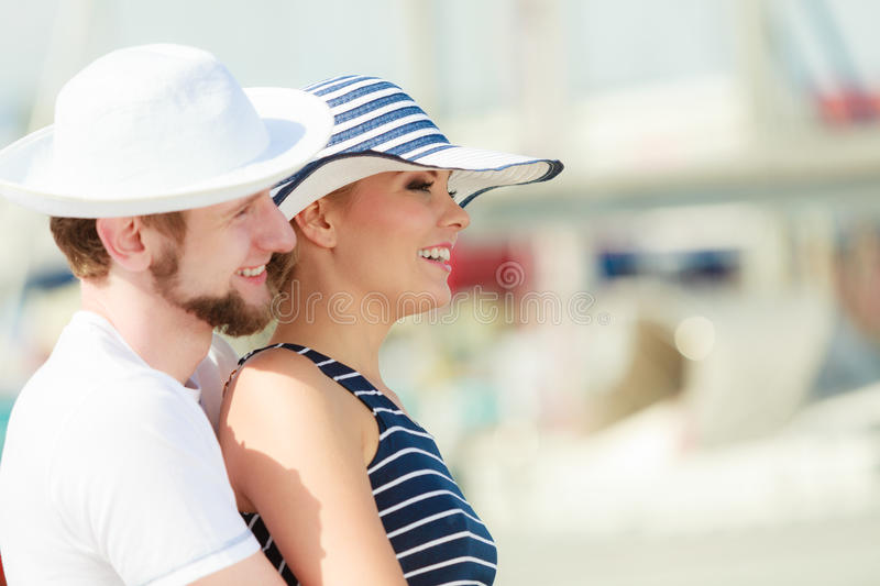 Tourist couple in marina against yachts in port. Travel tourism and people concept. Young tourist couple on vacation standing in front of boats in marina stock photo