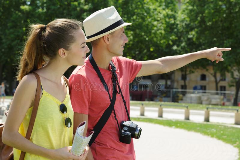 Tourist couple in park pointing into distance. Couple royalty free stock photo
