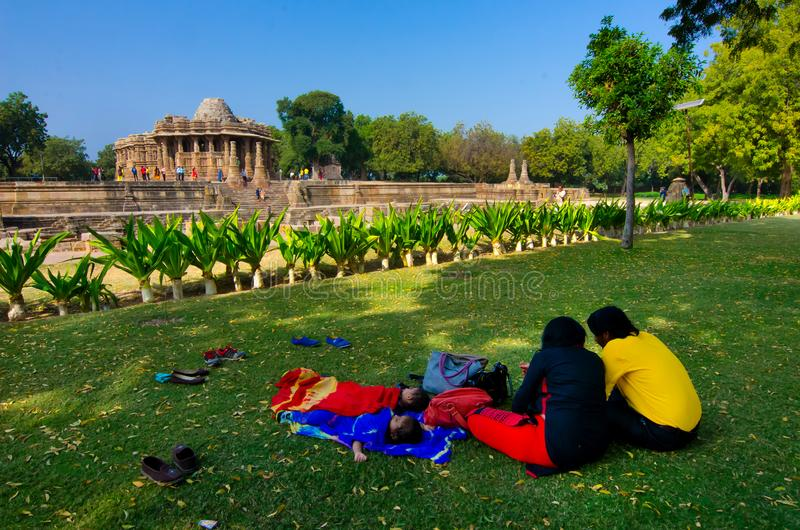 Tourist couple relaxing near The Sun Temple, Modhera, Gujarat, India. royalty free stock photography